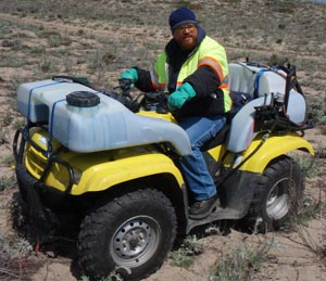 All Seasons Weed Control in Northern CA - Greg at the controls of Custom ATV sprayer with saddle tanks